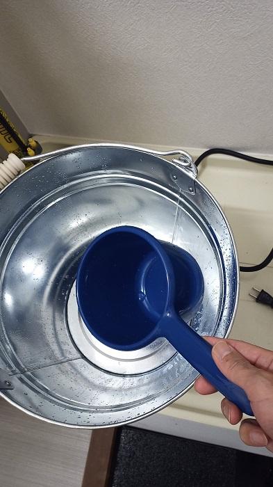バケツのお湯を手おけで汲んで身体を洗う