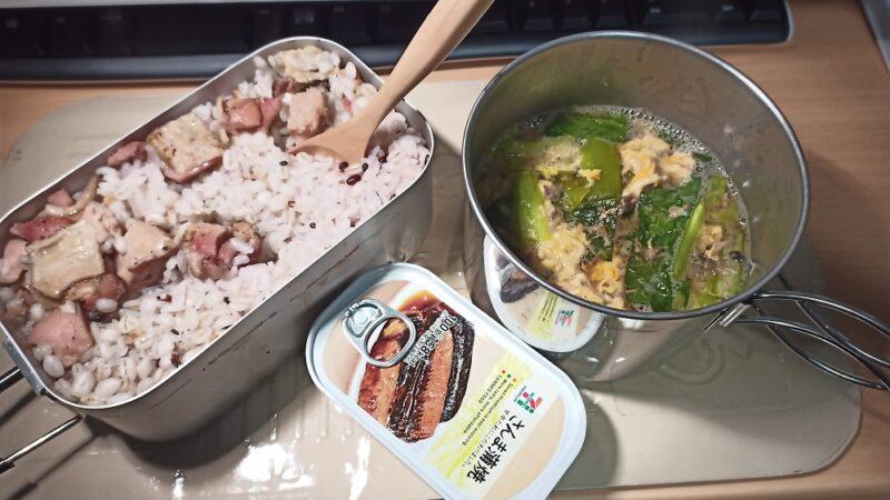 今日の夕食。焼き鳥缶を入れたご飯と、さんま蒲焼き缶、小松菜とサバの味噌煮缶と卵の汁物